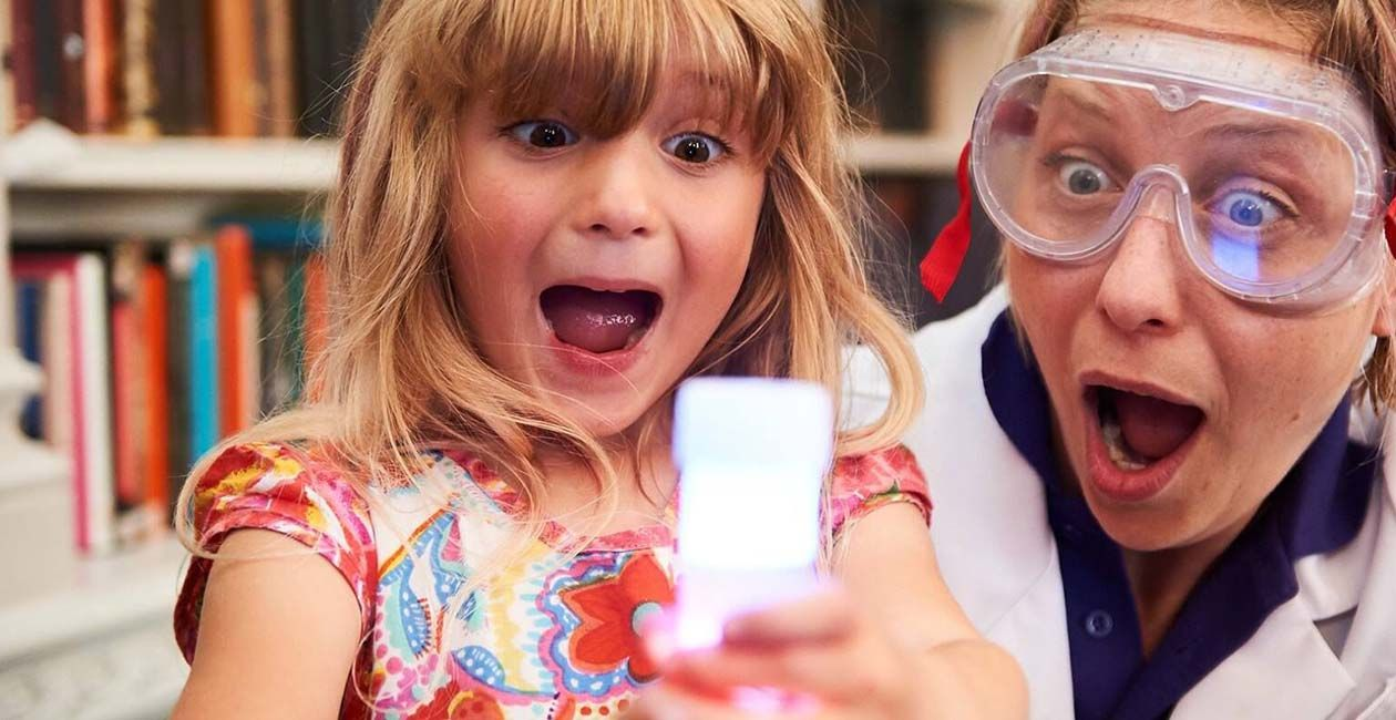 Excited girl and Mad Scientist looking at beaker filled with white liquid