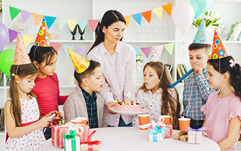 Mother holding a cake and kid blowing out candles.  5 other kids wearing party hats around the cake watching.