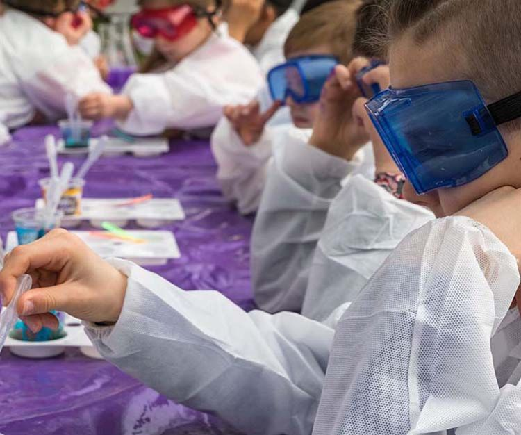 Kids wearing safety goggles pouring liquid into a mad science cup using a pipette